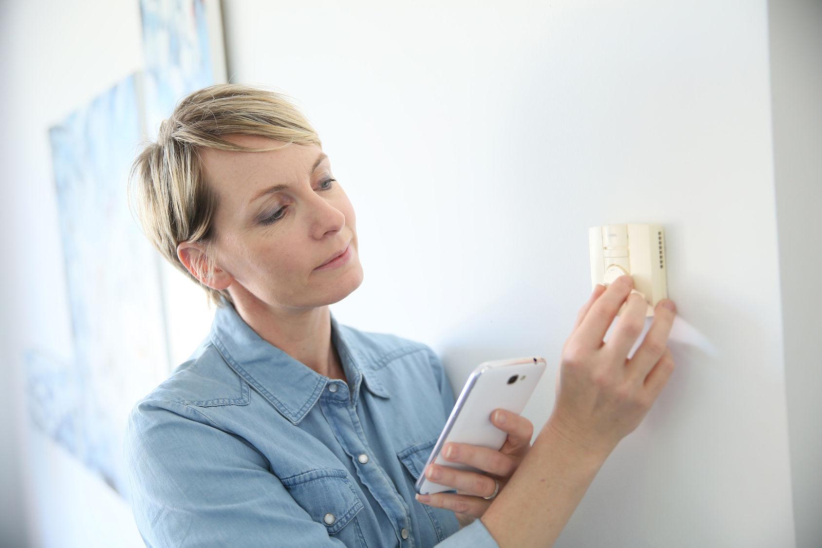 image d'une femme qui règle un thermostat
